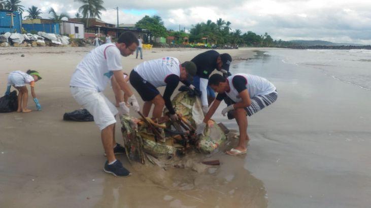 Foto: Voluntários retiram um sofá enterrado na areia da praia